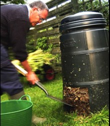 Man getting compost from a compost bin.