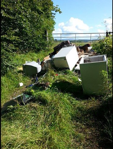 Fly-tipping on highway verge, blocking entrance to field.