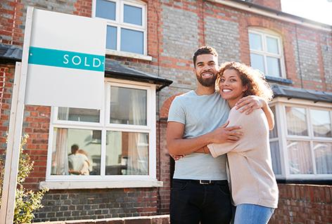 Couple nexgt to sold sign outside their new home